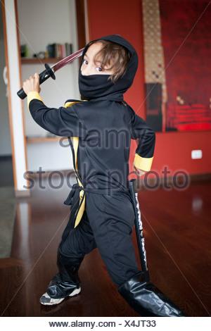 A boy dressed in a ninja costume swinging a samurai sword - Stock Photo
