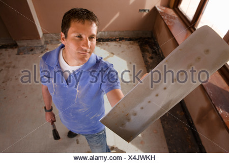 Man holding plastering trowel - Stock Photo