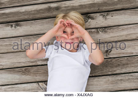 Portrait of little boy lying on a jetty shielding his eyes with his hands - Stock Photo
