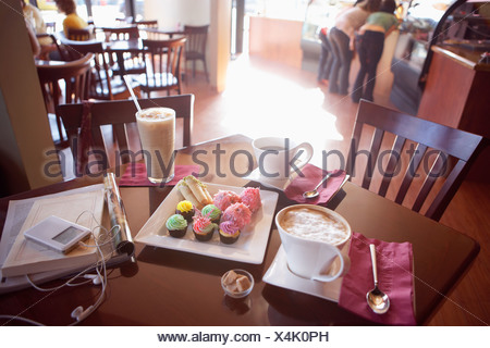 Iced coffee latte black coffee and cakes on serving dish beside MP3 player and publications on cafe table elevated view tilt st - Stock Photo