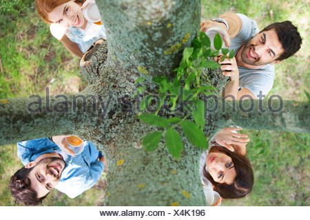Friends holding plastic cups at tree trunk - Stock Photo