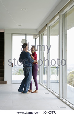 Mature couple dancing in empty living room - Stock Photo
