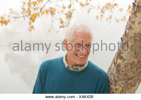 Senior man smiling and leaning against tree - Stock Photo