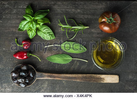 Vegetables and herbs on dark rustic wooden background. Greek black olives, fresh green sage, rosemary, basil herbs, oil, tomato, - Stock Photo