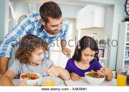 Cheerful man with children having breakfast - Stock Photo