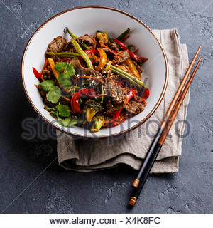 Szechuan beef stir fry with vegetables in bowl on dark stone background - Stock Photo