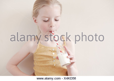 Young girl drinking glass of milk through straw - Stock Photo