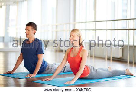Portrait of young woman and man doing exercise for stretching in gym - Stock Photo