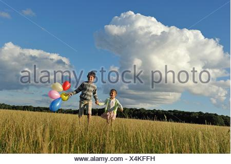 young boy with his sister running with balloons in a field, Ile-de-France, France, Europe. - Stock Photo
