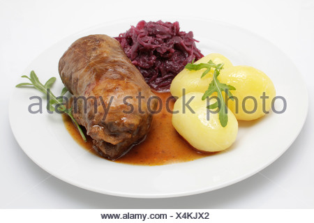 Stuffed beef roulade with gravy, red cabbage and boiled potatoes - Stock Photo