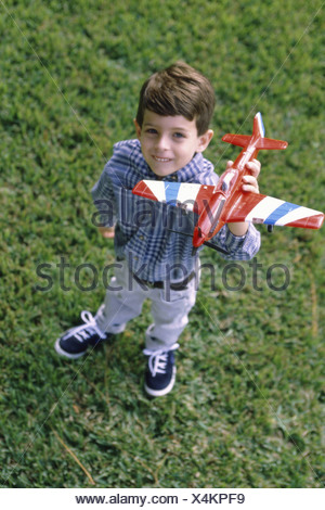 Portrait of a boy standing on a lawn holding a model airplane - Stock Photo