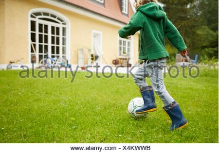 Rear view of boy wearing wellingtons playing football in the garden - Stock Photo
