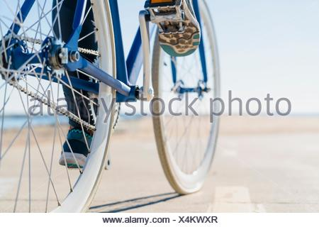 Woman cycling, low section, close-up - Stock Photo