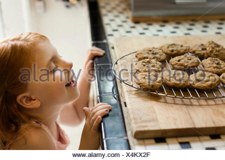 Girl peeking over kitchen counter at biscuits - Stock Photo