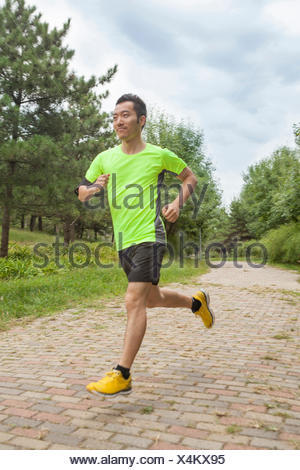 Young male runner running in park - Stock Photo