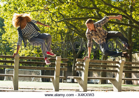 Couple leaping over park benches - Stock Photo