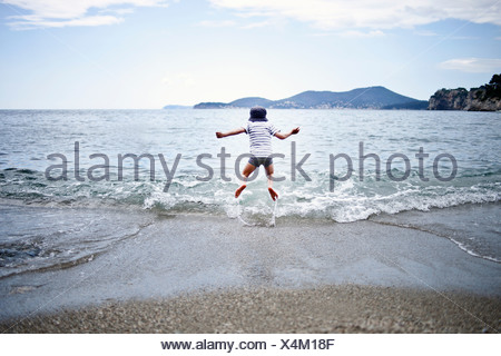 Little boy jumping into the sea - Stock Photo