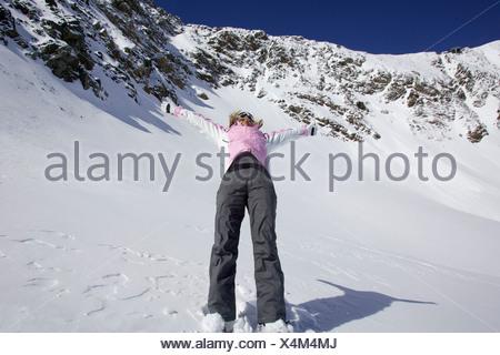 Woman skiing backwards down slope - Stock Photo