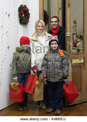 Family returning home from christmas shopping - Stock Photo