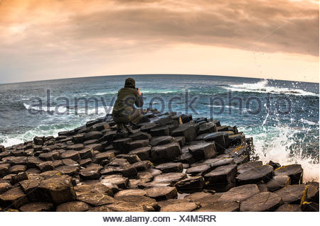 Man taking photo with a smartphone, Giant's Causeway, basalt columns, Causeway Coast, County Antrim, Northern Ireland - Stock Photo