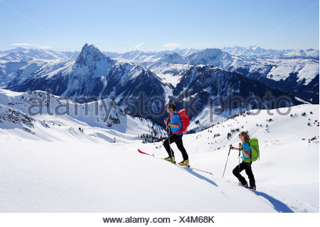 Two backcountry skiers ascending to Brechhorn, Grosser Rettenstein in background, Kitzbuehel Alps, Tyrol, Austria - Stock Photo