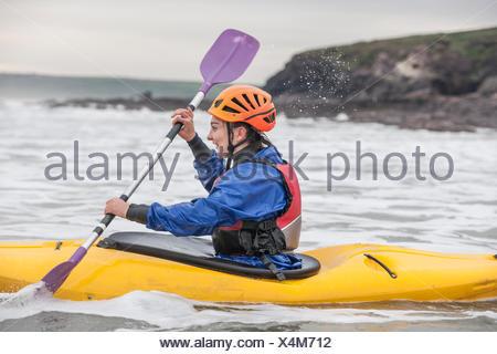 Young woman sea kayaking - Stock Photo