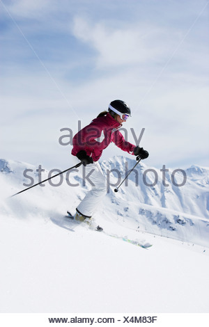 Woman in red & white outfit off-piste. - Stock Photo