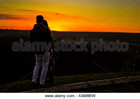 Couple Embracing While Standing On Cliff Against Sky During Sunset - Stock Photo