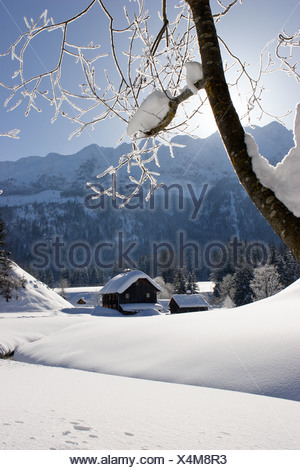 a old wooden house on a creek and a lot of snow Krungl Styria Austria - Stock Photo