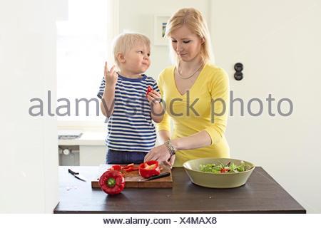 Finland, Helsinki, Kallio, Mother and son making salad in kitchen - Stock Photo