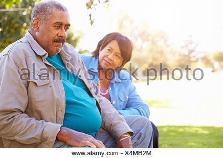 Senior Woman Comforting Unhappy Senior Husband Outdoors - Stock Photo