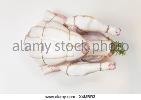 Raw Turkey with bacon slices, elevated view - Stock Photo