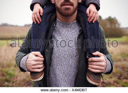 Close Up Of Father Gives Son Ride On Shoulders During Walk - Stock Photo