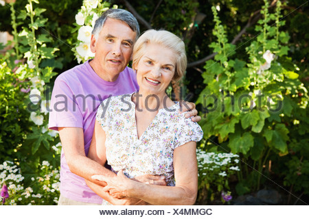 portrait of  mature couple in garden. - Stock Photo