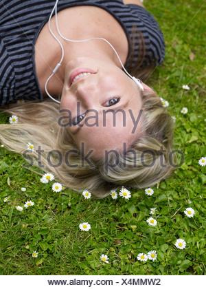 Smiling woman listening to headphones - Stock Photo