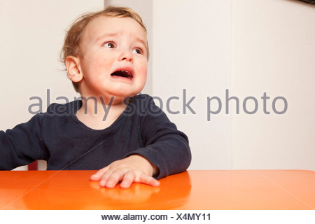 Little boy sitting on table crying - Stock Photo