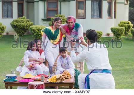 Man filming his family with a home video camera on holi - Stock Photo