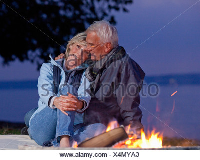 A senior couple sitting beside a campfire embracing - Stock Photo
