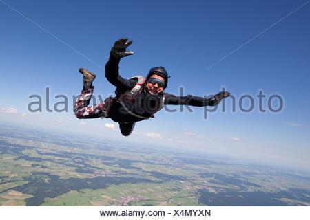 Man skydiving over rural landscape - Stock Photo