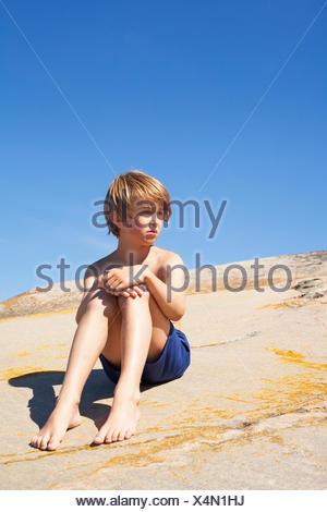 Sweden, Uppland, Runmaro, Barrskar, Portrait of boy (6-7) sitting on rock in summer - Stock Photo
