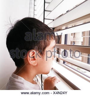 Portrait of a boy looking through the window - Stock Photo