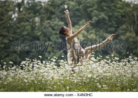 Woodstock New York USA woman dancing in field of wild flowers - Stock Photo