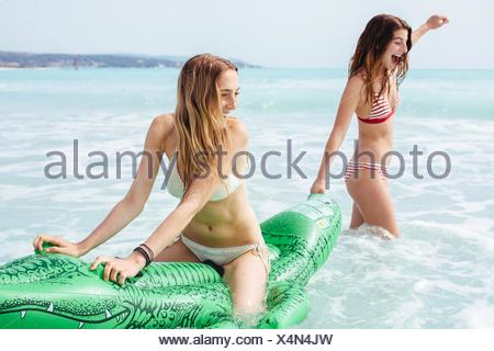 Two young female friends wearing bikinis playing on inflatable crocodile in sea - Stock Photo