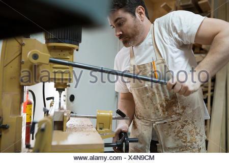 Carpenter using drill press in workshop - Stock Photo