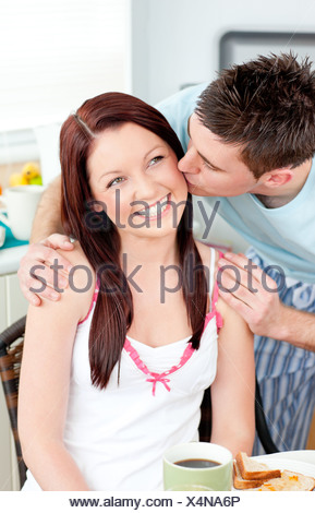 Attentive boyfriend kissing his girlfriend at her cheek during breakfast in the kitchen - Stock Photo