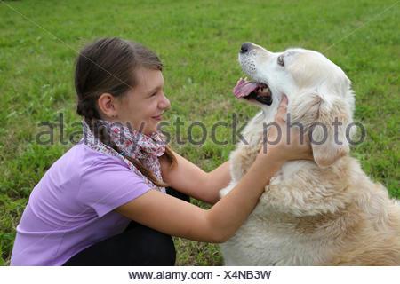 Mädchen schmust mit einem Hund - Stock Photo