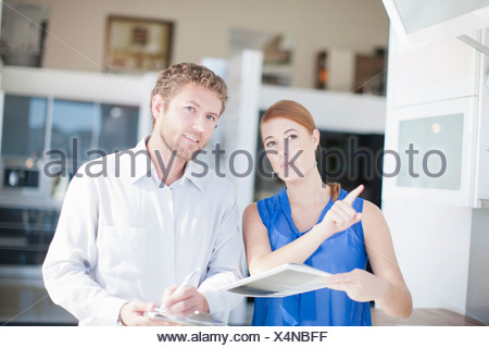 Young couple in kitchen showroom - Stock Photo