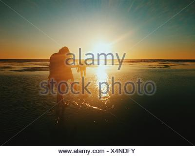 Silhouette People Walking On Beach At Sunset - Stock Photo