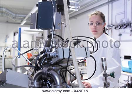 Portrait of female lab technician with scientific equipment - Stock Photo