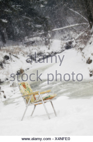 Folding chair in the snow - Stock Photo